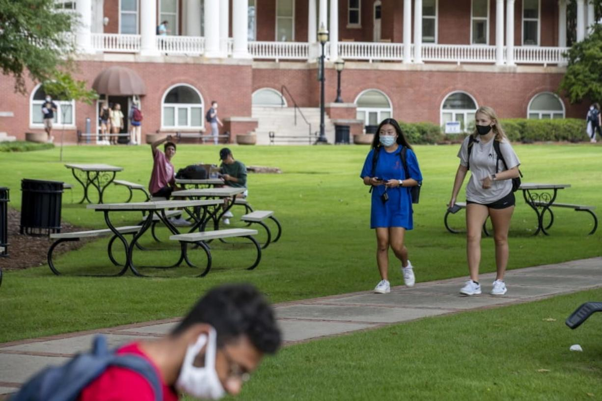 FILE - In this Aug. 21, 2020, file photo, Georgia College and State University freshmen Ashlynn Anglin, right, and Meghan Murphy, second from right, wear face masks as they talk while walking through the campus in Milledgeville, Ga. As more and more schools and businesses around the country get the OK to reopen, some college towns are moving in the opposite direction because of too much partying and too many COVID-19 infections among students.