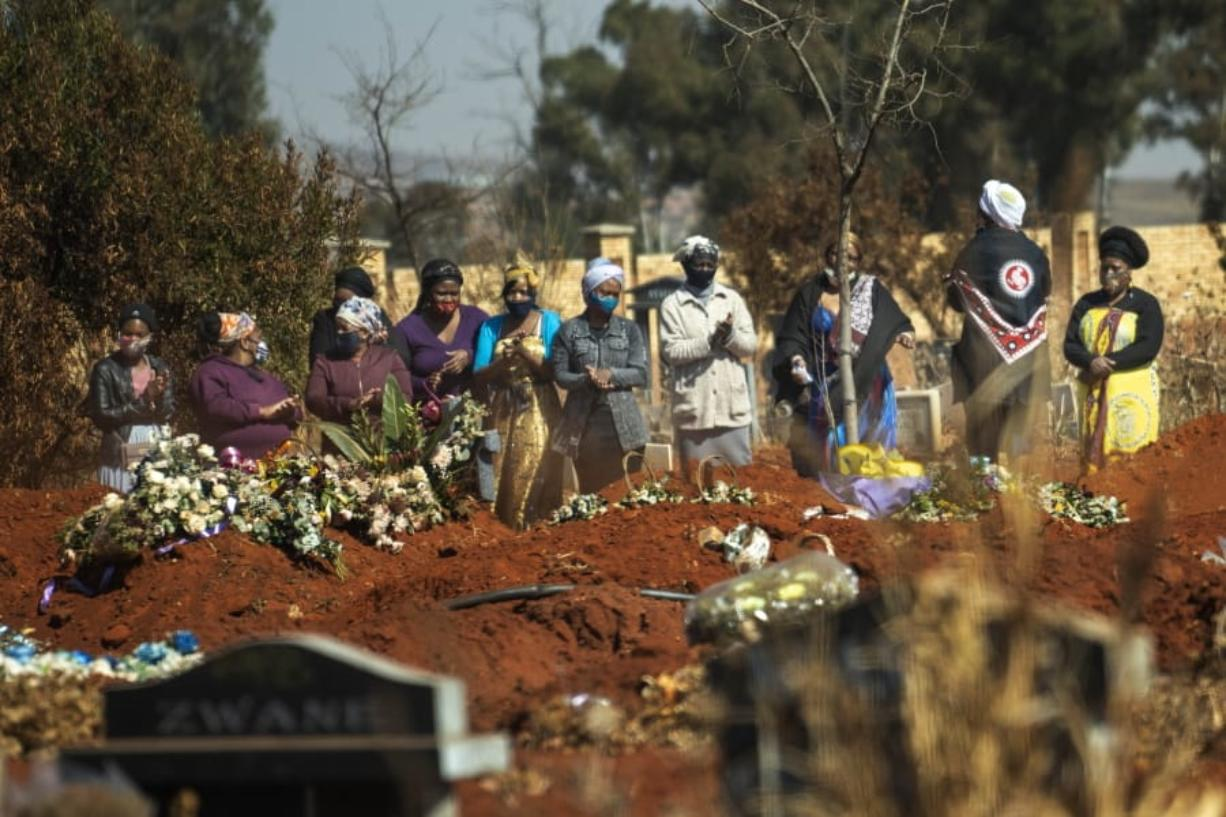 Mourners pray during a burial ceremony Thursday at the Olifantsveil Cemetery outside Johannesburg, South Africa. The frequency of burials in South Africa has significantly increased during the coronavirus pandemic.