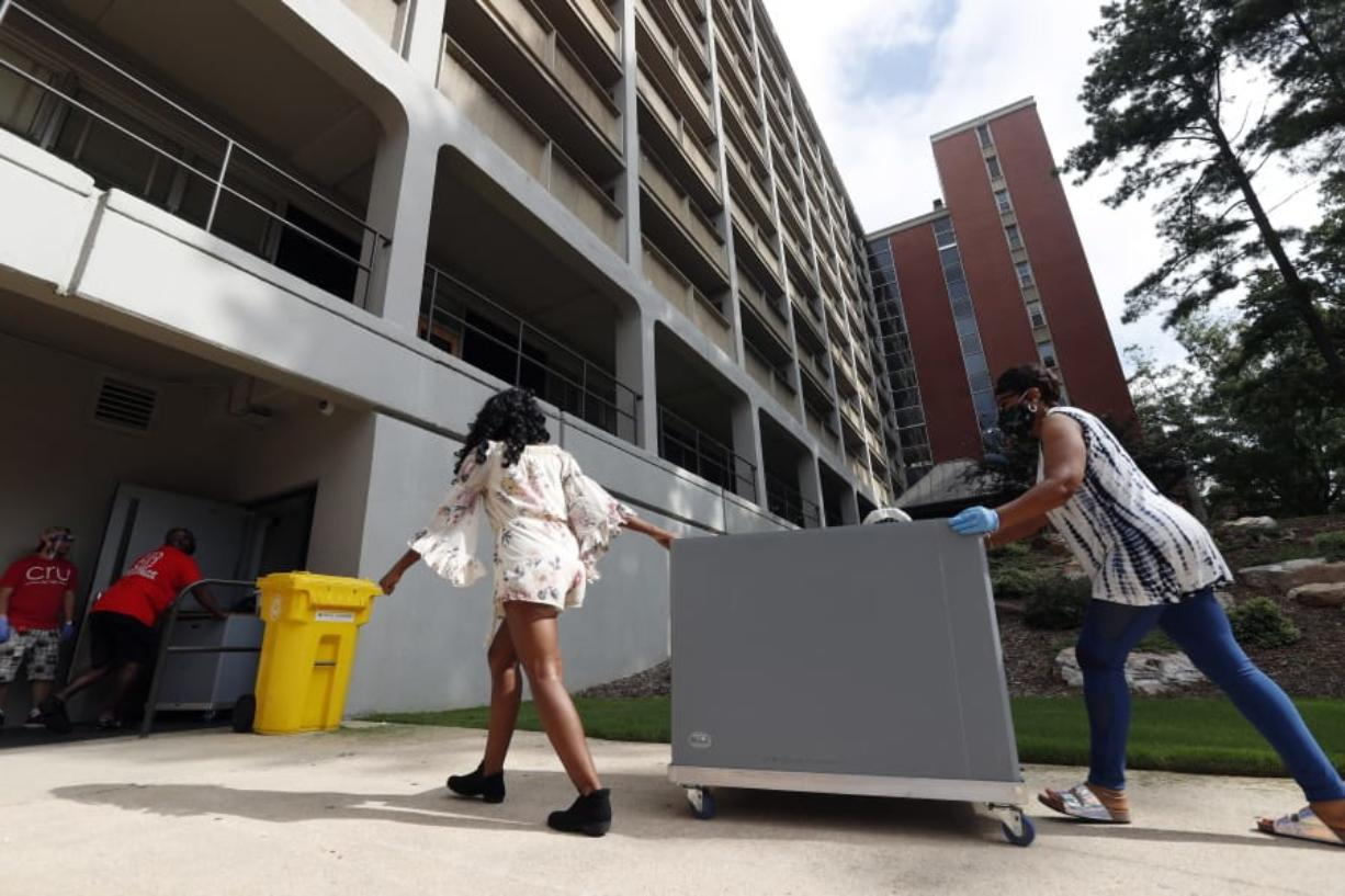 College students begin moving in for the fall semester at N.C. State University in Raleigh, N.C., Friday, July 31, 2020. The first wave of college students returning to their dorms aren't finding the typical mobs of students and parents. At N.C. State, the return of students was staggered over 10 days and students were greeted Friday by socially distant volunteers donning masks and face shields. .