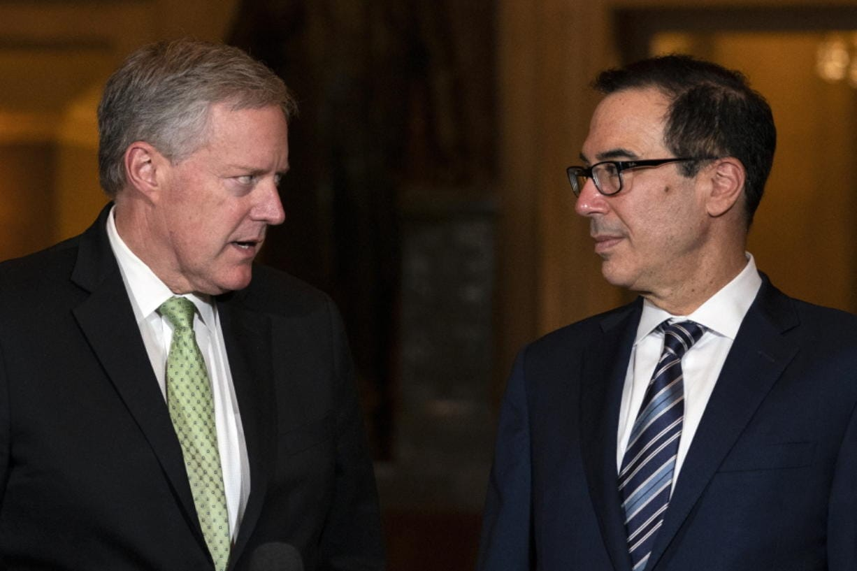 Treasury Secretary Steven Mnuchin and White House chief of staff Mark Meadows look to each other as they speak to reporters on Capitol Hill in Washington, Thursday, Aug. 6, 2020.