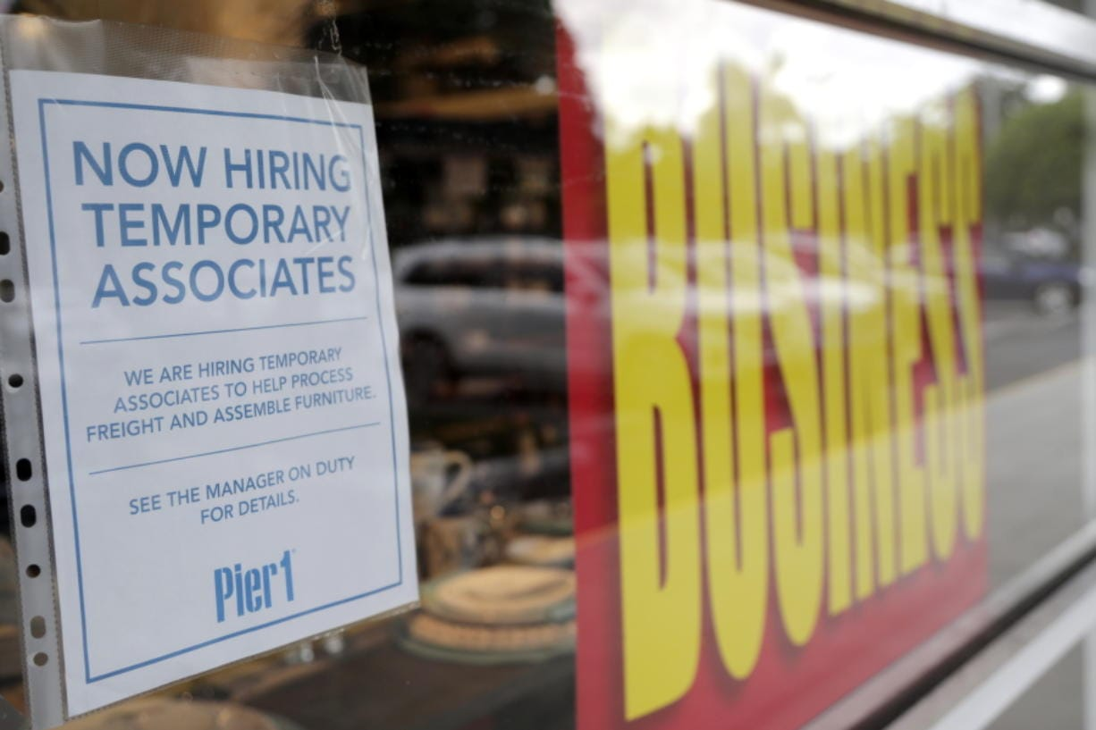 A sign advertises hiring of temporary associates at a Pier 1 retail store, which is going out of business, during the coronavirus pandemic, Thursday, Aug. 6, 2020, in Coral Gables, Fla. The home goods retailer is going out of business and is permanently closing all of its stores.