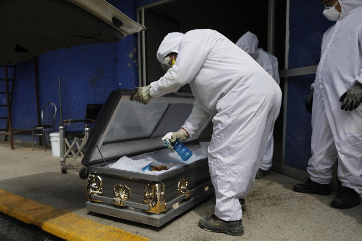 A worker wearing protective gear sprays disinfectant solution inside the coffin of a person who died from suspected COVID-19, as the body arrives Monday at the crematorium at Xilotepec Cemetery in Xochimilco, Mexico City.
