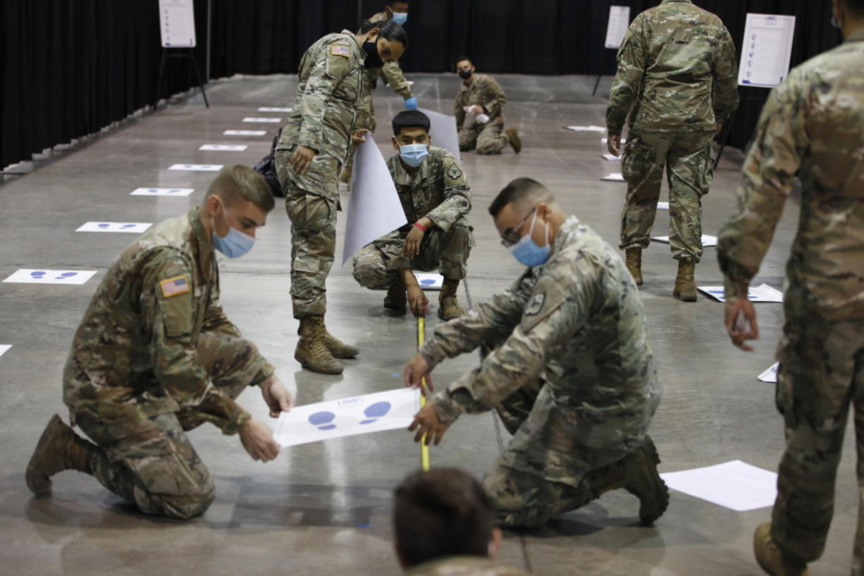 Members of the Nevada National Guard install social distancing stickers while setting up a new temporary coronavirus testing site Monday, Aug. 3, 2020, in Las Vegas.