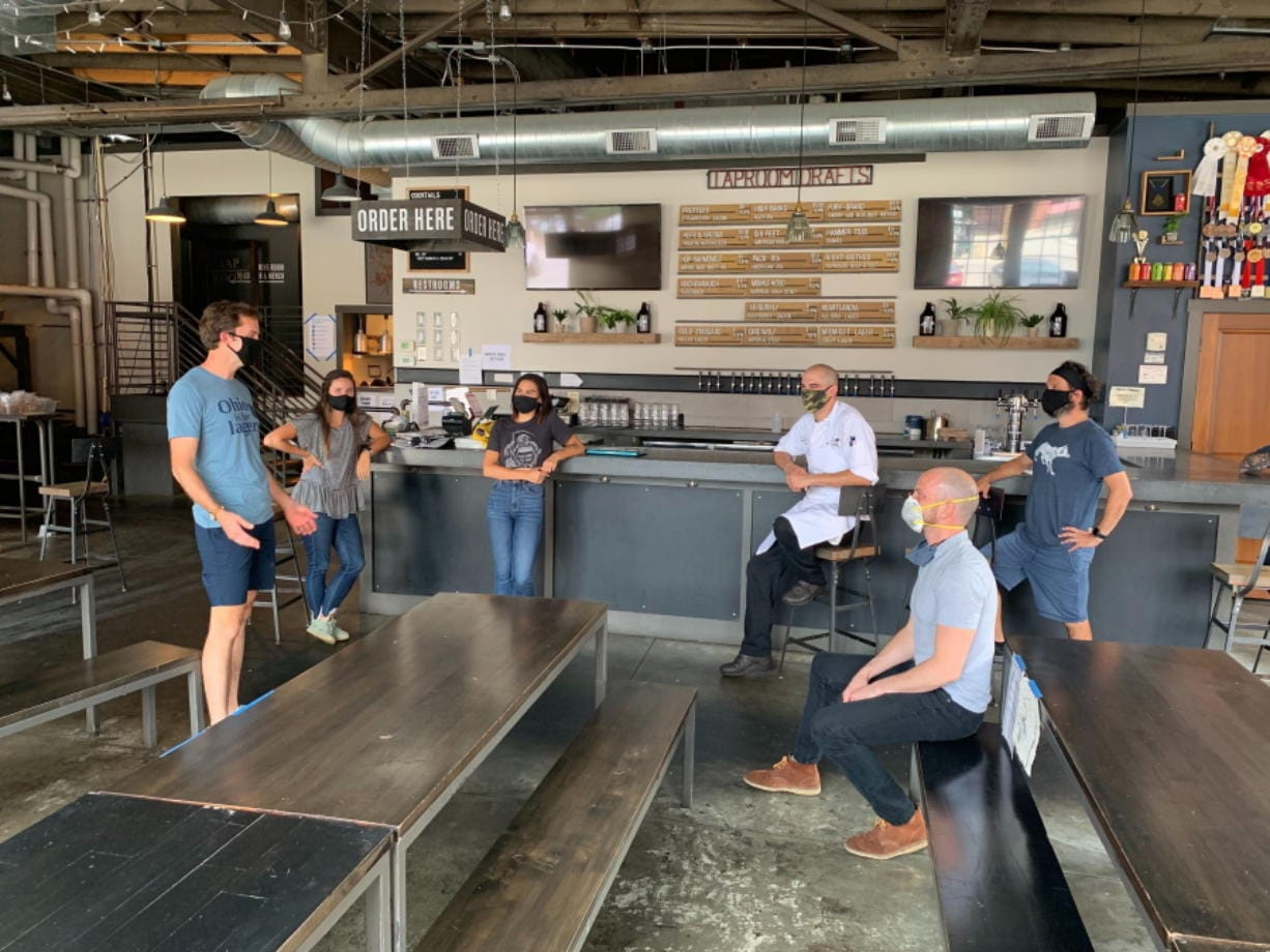 In a July 2020 photo provided by Wolf's Ridge Brewing, owner Bob Szuter, employees Allison Randolph and Alicia Herrmann, sous chef Andy Zamagias, general manager Corey Schlosser and employee Andy Powell, from left, gather inside the restaurant's tap room in Columbus, Ohio. Szuter says he's trying to figure out new ways to bring in revenue, focusing more on the brewery side of the business until it's safe to have a full dining room.