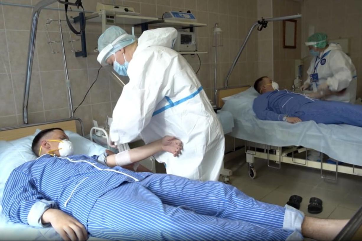 In this photo made from footage provided by the Russian Defense Ministry on Wednesday, July 15, 2020, medical workers in protective gear prepare to draw blood from volunteers participating in a trial of a coronavirus vaccine at the Budenko Main Military Hospital outside Moscow, Russia. Russia is boasting that it's about to be the first country to approve a COVID-19 vaccine, but scientists worldwide are sounding the alarm that the headlong rush could backfire.