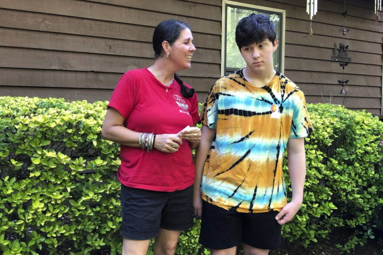 Molly Ball talks to her son Henry about plans to send him back to in-person classes this fall, as they stand outside their house in Woodstock, Ga., Thursday, July 23, 2020. Ball says she thinks Henry and his brother William need the structure and routine of in-person classes, but has regrets about not keeping them home to learn virtually amid the COVID-19 pandemic. Cherokee County, near Atlanta, is one of many districts nationwide that gave parents a choice between in-person and all-online classes this fall.