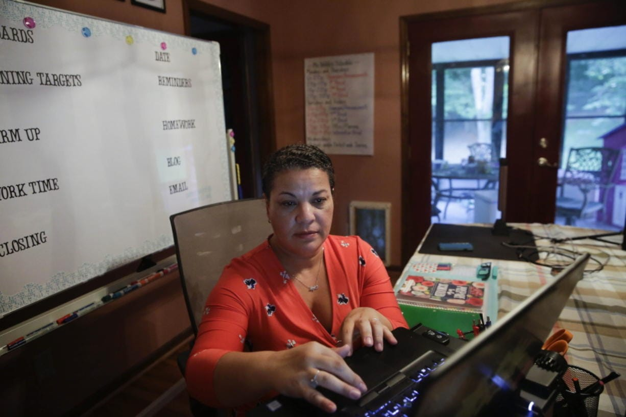 Aimee Rodriguez Webb works on her computer Tuesday at her dinning room table that she set up as a virtual classroom for a Cobb County school in Marietta, Ga. After a rocky transition to distance learning last spring, Webb is determined to do better this fall.