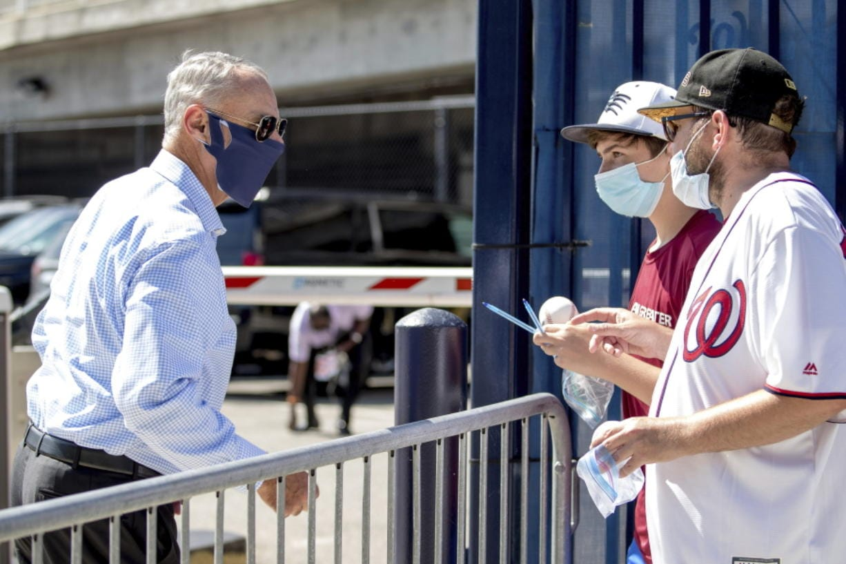 MLB Commissioner Rob Manfred, left, speaks with fans as he arrives at Nationals Park for the New York Yankees and the Washington Nationals opening day baseball game, Thursday, July 23, 2020, in Washington.