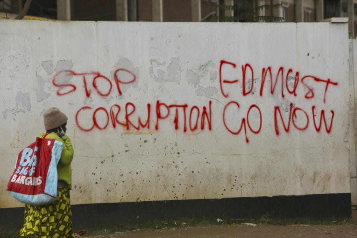 A woman walks past a wall with graffiti calling on the government to stop corruption in this Monday, June, 15, 2020 photo.