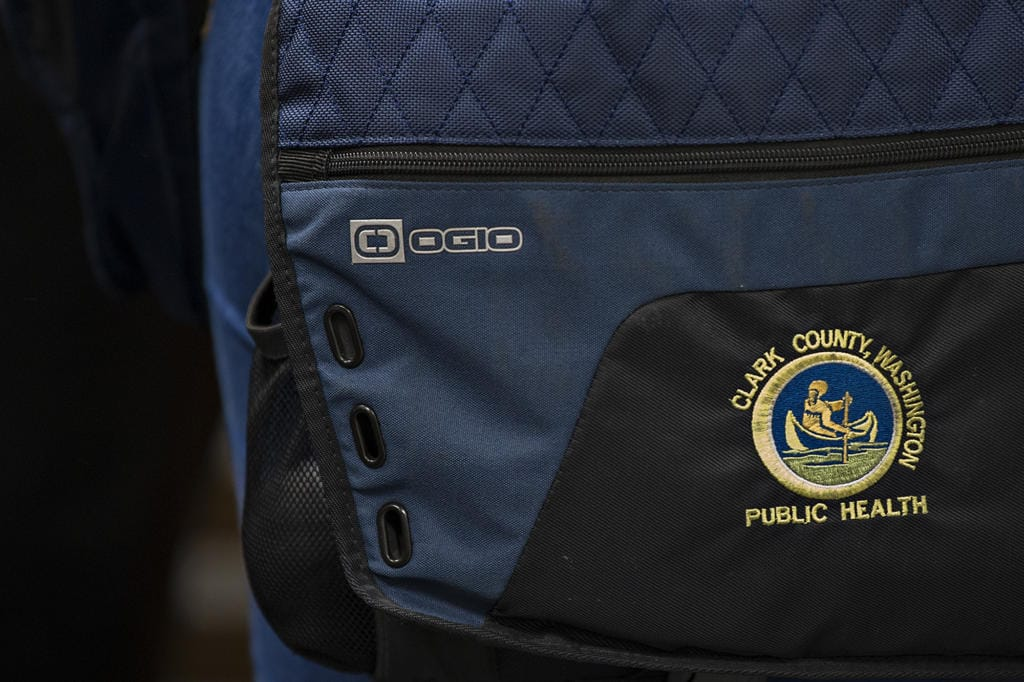 A patch is seen on the bag of Clark County Public Health Environmental Health Specialist Maggie Yaddof before inspecting the Fargher Lakehouse in Yacolt on Jan. 13.