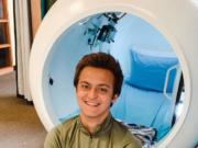 "Alec Marshall poses in front of a hard-shell hyperbaric chamber at In Light Hyperbarics. The chamber is called ""Moby Dick"" because it looks like a big, white whale."
