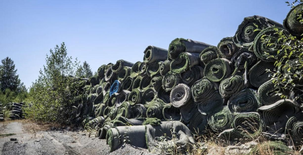 Piles of old FieldTurf are stored near the Puyallup River. FieldTurf was used for a recent retrofit for the liner of the Electron Hydropower Project.
