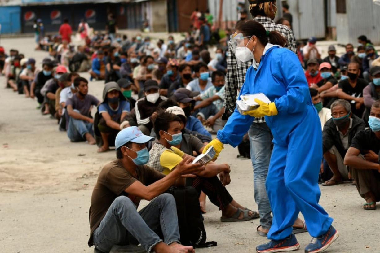 Volunteers distribute food packets people in need after a week-long restrictions were imposed by district officials to contain the spread of the Covid-19 coronavirus, in Kathmandu on August 31, 2020.