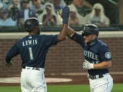 Seattle Mariners' Kyle Seager, right, is congratulated by teammate Kyle Lewis after hitting a two-run home run off of Texas Rangers starting pitcher Kolby Allard during the first inning Monday in Seattle. The Mariners have won six straight games for the first time since July 2019.