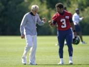 Seattle Seahawks quarterback Russell Wilson (3) bumps fists with head coach Pete Carroll after practice last week in Renton. With Wilson in the prime of his career and surrounded by weapons on offense, the Seahawks are once again contenders in the NFC. (Ted S.