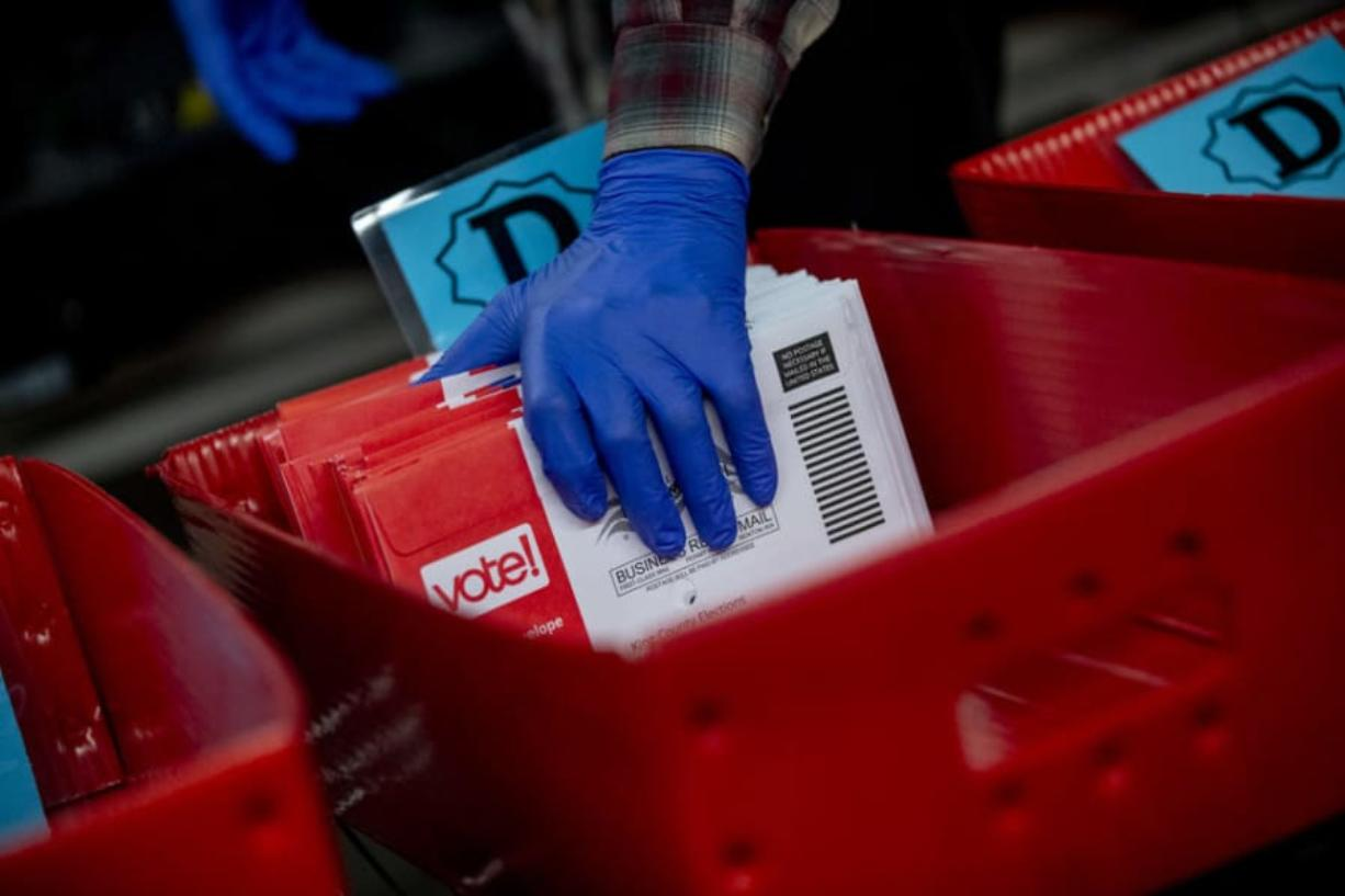 Ballots are processed at the King County Elections headquarters in Renton for Washington stateCfUs primary election on March 10, 2020. Though gloves have always been optional for elections workers, it has become mandatory to prevent COVID-19.