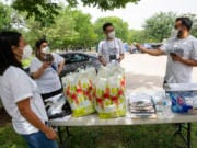 Ramiro Luna-Hinojosa, right, speaks to members of Somos Tejas at Martin Weiss Park before they go door to door in the Oak Cliff neighborhood educating people on COVID-19, the census and voting on June 27, 2020, in Dallas.