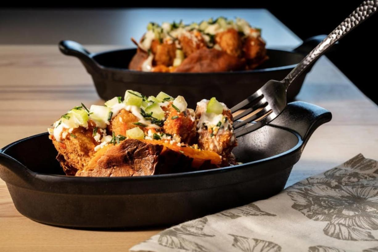 The classic idea of a loaded baked potato becomes dinner all by itself. Here sweet potatoes take the place of russets, and Buffalo chicken wings inspire the toppings.