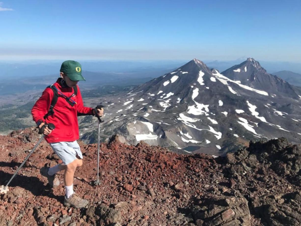 Mason Morical, 12, of Bend, Ore., walks across the summit of South Sister on Aug. 15. In the background, Middle Sister, left, and North Sister, right, can be seen from the summit.