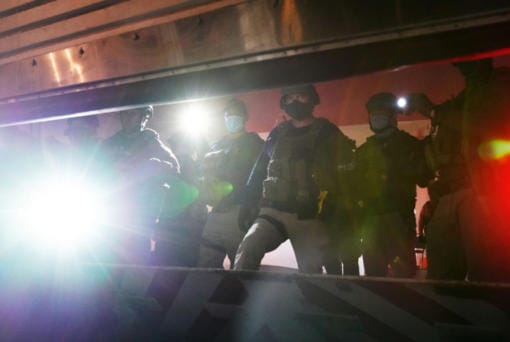 Federal officers shine flashlights from inside a closing garage door at the rear entrance to the Mark O. Hatfield U.S. Courthouse on July 31, 2020 in Portland, Oregon.