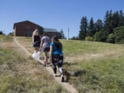 Washington State University Vancouver biology graduate students Samantha Bussan, left, Rebekah Gaxiola and Kelsey King take a shortcut after visiting a campus meadow they intend to replant with native wildflowers.