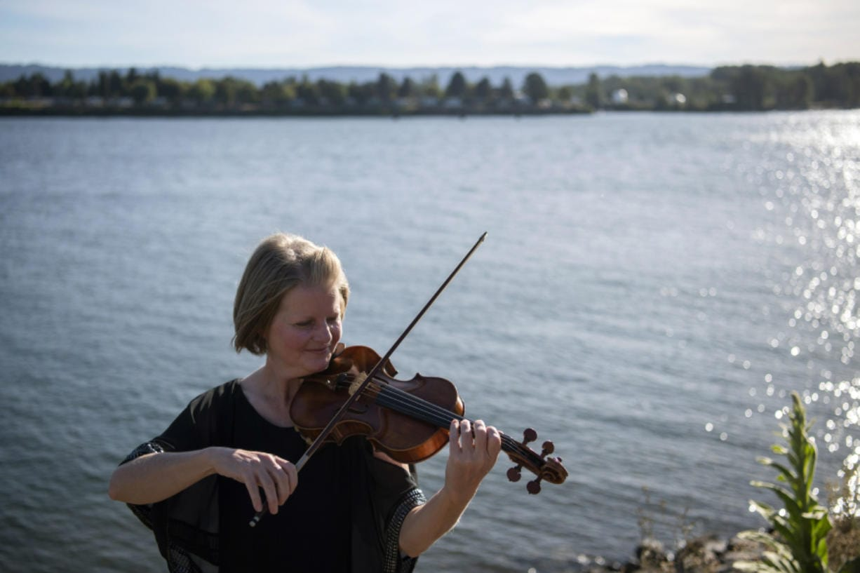 The Vancouver Symphony Orchestra's upcoming online concert will feature a reduced group of musicians -- mostly string players such as concertmaster Eva Richey, pictured here at the Vancouver waterfront on a recent evening. No breath-powered instruments will be part of the concert because of the risk of coronavirus transmission.