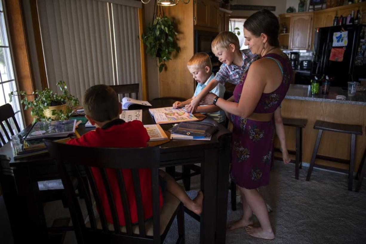 Oliver Emerick, 6, from left, does math problems with his cousin Mavric Martin, 5, as Mavric's brother Hendric, 3, and their mother, Chelsey Martin, help them at their home in Battle Ground on Sept. 4. Chelsey Martin and her sister-in-law Kati Emerick have joined forces to teach their sons kindergarten amid school closures and health concerns due to the coronavirus pandemic.