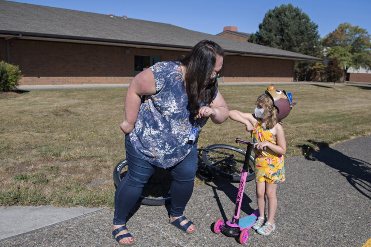 Kindergarten teacher Miranda Roderick, left, greets kindergartner Avery Anderson, 5, as she cruises by River HomeLink with her family to pick up materials for the upcoming school year. Enrollment in Alternative Learning Experiences, such as River HomeLink, is up while school districts operate remotely.