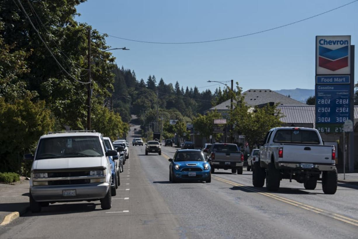 Drivers on Main Street in Battle Ground pass parked cars along both sides of the road Thursday morning.