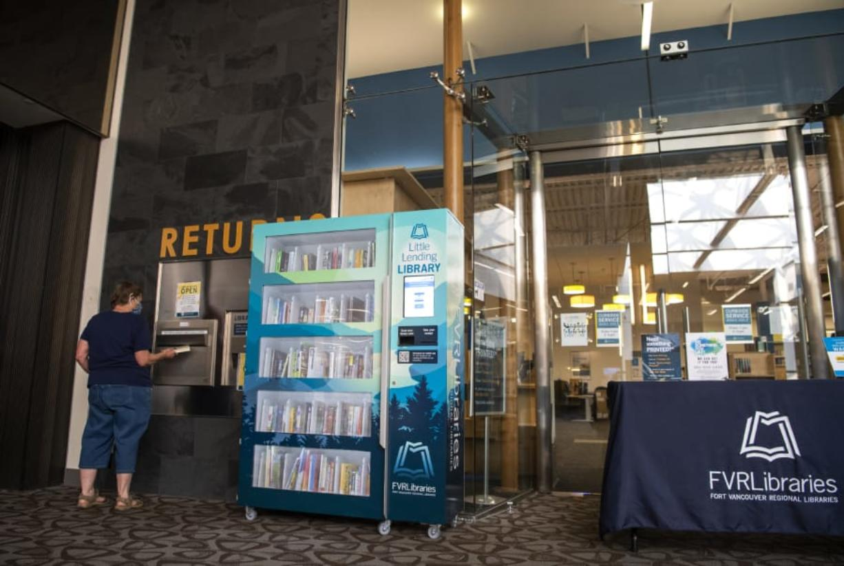 Deborah Carter of Vancouver returns books next to the Little Lending Library, a machine that allows visitors to browse a small selection of books while the Vancouver Mall library branch remains closed due to the coronavirus pandemic.