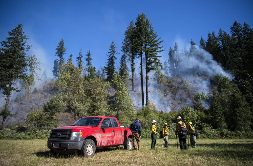 Fire crews work the Washougal River Road fire just past mile marker 5 Tuesday morning outside of Washougal. As of Tuesday morning, the fire, likely caused by a power line, was about 10 acres and 20 percent contained.