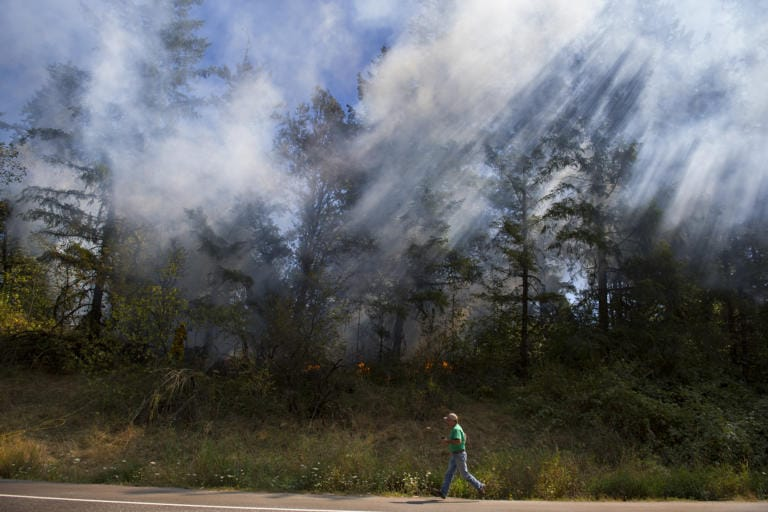 A man runs toward firefighters as sunlight illuminates smoke from a fire along Lewisville Highway on Tuesday afternoon, Sept. 8, 2020. Firefighters were called to the scene and promptly extinguished the blaze. Traffic was routed around the scene. (Amanda Cowan/The Columbian)