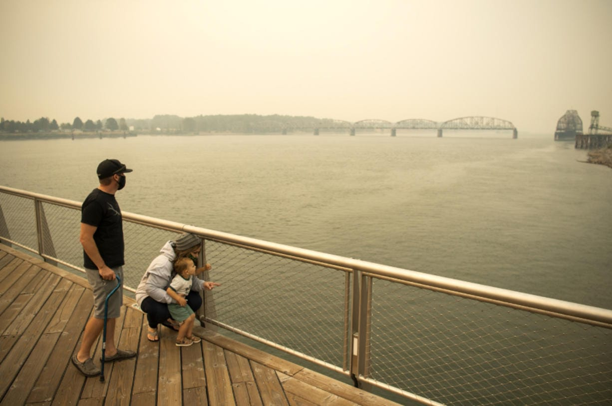 Brent McCarthy, from left, and Marissa Matthews, play on the pier Thursday at The Waterfront Vancouver with their son Xavier, 2. The family lives outside of Salem, Ore., and evacuated Tuesday to escape the smoke and fire risk. Matthews has cancer and is extra sensitive to the smoke, so although their area was still on level 2 evacuation, they decided to leave early to stay safe.