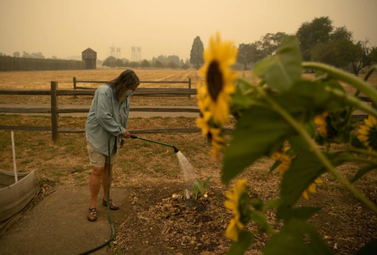 """Heisson resident and volunteer Elizabeth Stoltz waters the Fort Vancouver Garden in Vancouver on Friday. Stoltz said things were dried out because of the wind and smoke. """"The wind sucks the life out of everything,"""" she said. Stoltz is still not under evacuation from the Big Hollow Fire, but her family made a plan in case it gets to that point."""