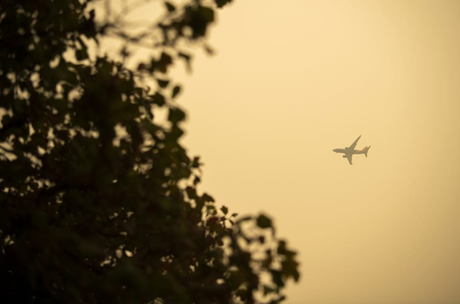 A plane passes over Fort Vancouver National Historic Site on Friday. The Portland and Seattle metro areas registered the worst air quality in the world Friday, as air quality remained in the hazardous range.