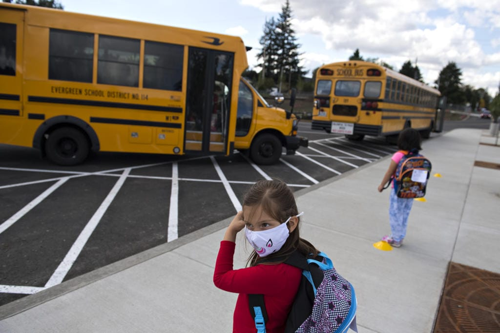 Kindergartner Evalynn Pratt, 5, secures her face mask while waiting for classmates to arrive on the bus at Sifton Elementary School on Tuesday afternoon, Sept. 22, 2020.