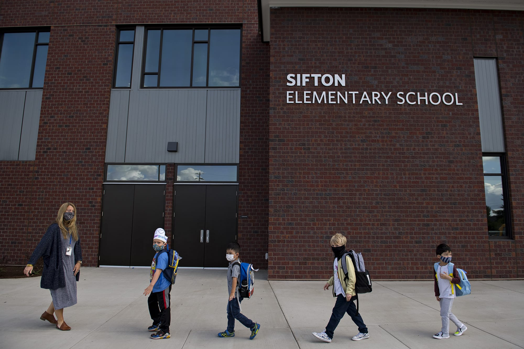 Kindergarten teacher Katie Plamondon, from left, leads students Phoenix Winmil, 5, Wes Charuchinda, 5, Emery Thomas, 6, and Jay Chou, 6, into the building for their second day of classes at Sifton Elementary School on Tuesday afternoon, Sept. 22, 2020. (Amanda Cowan/The Columbian)