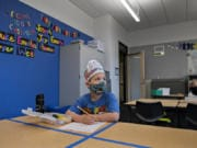 """Kindergartner Phoenix Winmil, 5, wears a hat that says """"I Love Kindergarten"""" as he tackles schoolwork on the second day of classes at Sifton Elementary School on Tuesday afternoon. Students are isolated to their own table rather than the typical arrangement of four students to one large desk. Students are also given their own sets of supplies that can be disinfected after class is over."""