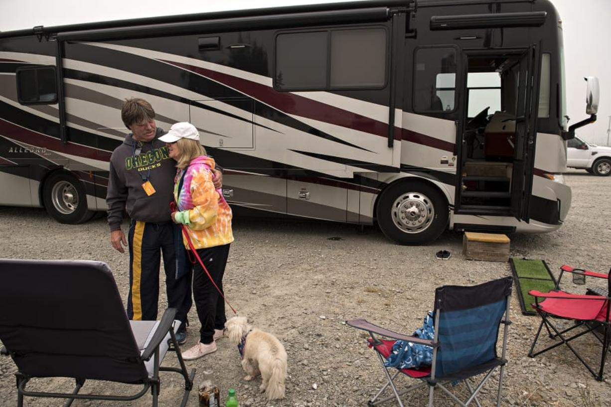 """Doug Lewis of Canby, Ore., embraces his partner, Judi Christiansen, while joined by her dog, Josie, 17, in the parking lot at ilani on Saturday. The pair were also joined by Lewis' sister, Bev, who is the owner of the motor home they are sleeping in. The three are staying in the casino parking lot as they escape the wildfires burning near their homes in Oregon. """"We don't know what we're going to come back to,"""" Lewis said."""
