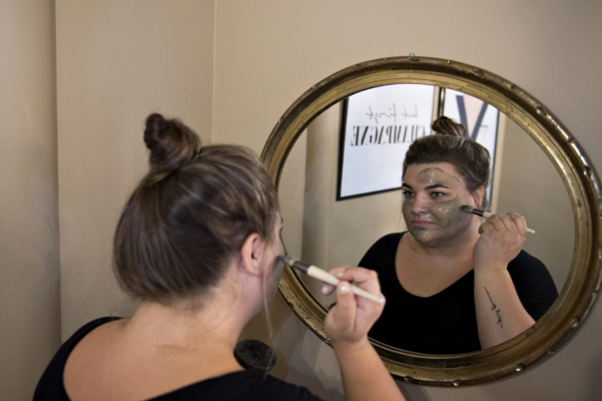 Salon manager Alex James demonstrates an Epicuren green tea and seaweed smoothing mask at Glam Beauty Bar in downtown Vancouver. James and other spa staff normally wear masks while in the salon.