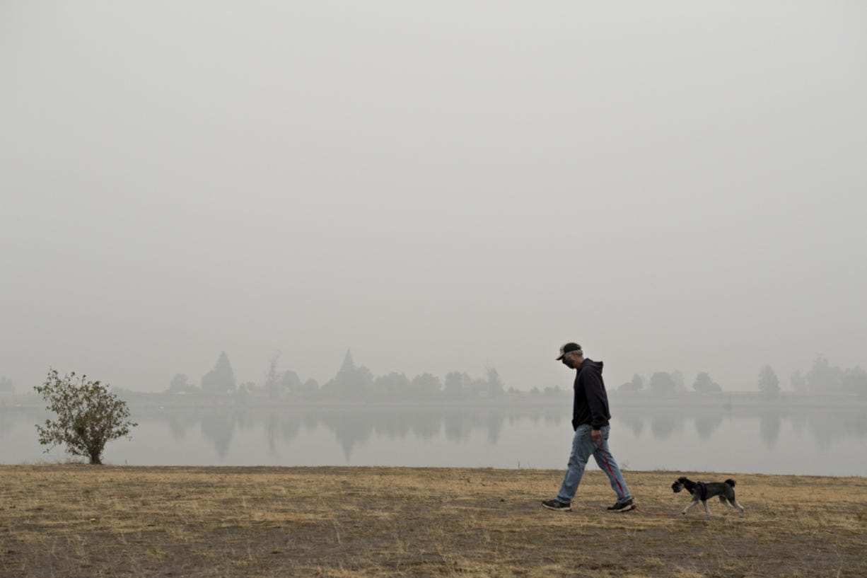 """Vancouver resident Frank Schmit wears a mask while taking his dog, Ripley, a miniature schnauzer, for a stroll as thick wildfire smoke obscures the visibility of trees across the water at Frenchman' Bar Regional Park. Schmit said the fires and the smoke are just the latest in a list of unusual events that have happened in 2020. """"It's been a hell of a year,"""" he said."""