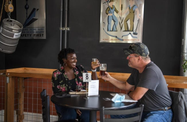 Bella Roushall, left, and her husband, Scott, enjoy beers together Saturday at Trusty Brewing in Vancouver.