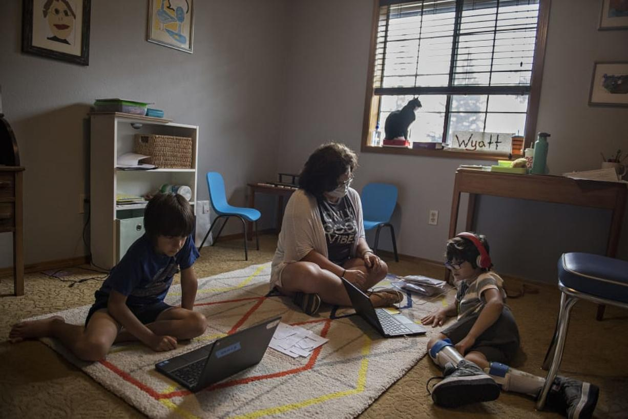 Rowan Lovato, 7, left, tackles schoolwork on his laptop while joined by tutor, Cheryl Davey, his twin brother, Wyatt, 7, and family cat, Jolene, at their Vancouver home Friday afternoon. The Lovato family is struggling to navigate digital learning, with one son with cerebral palsy, single mother Jill Lovato working full time and other obstacles.