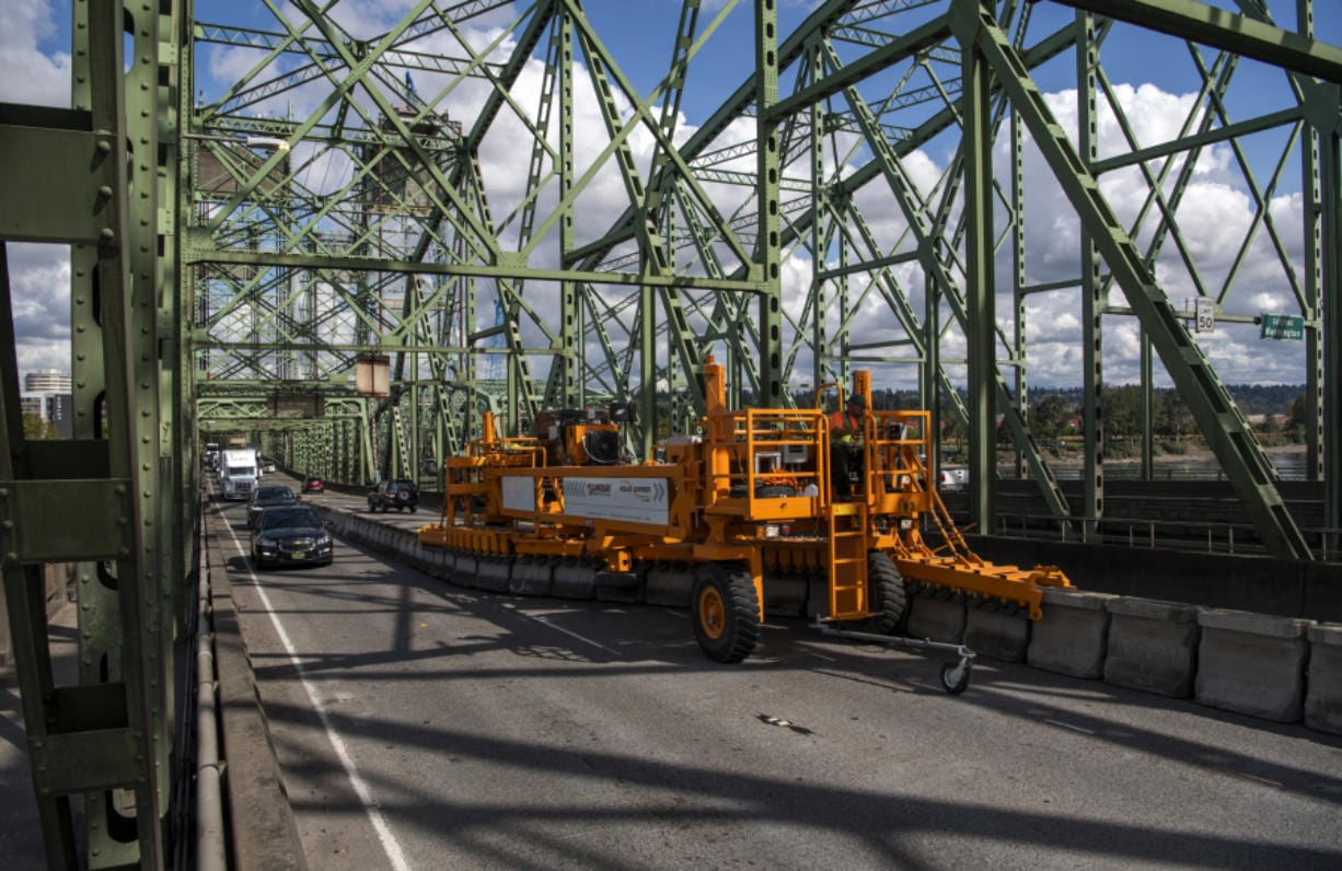 The zipper machine makes its way across the Interstate 5 Bridge to adjust the central barrier and reverse the middle lane of traffic shortly after noon Tuesday.