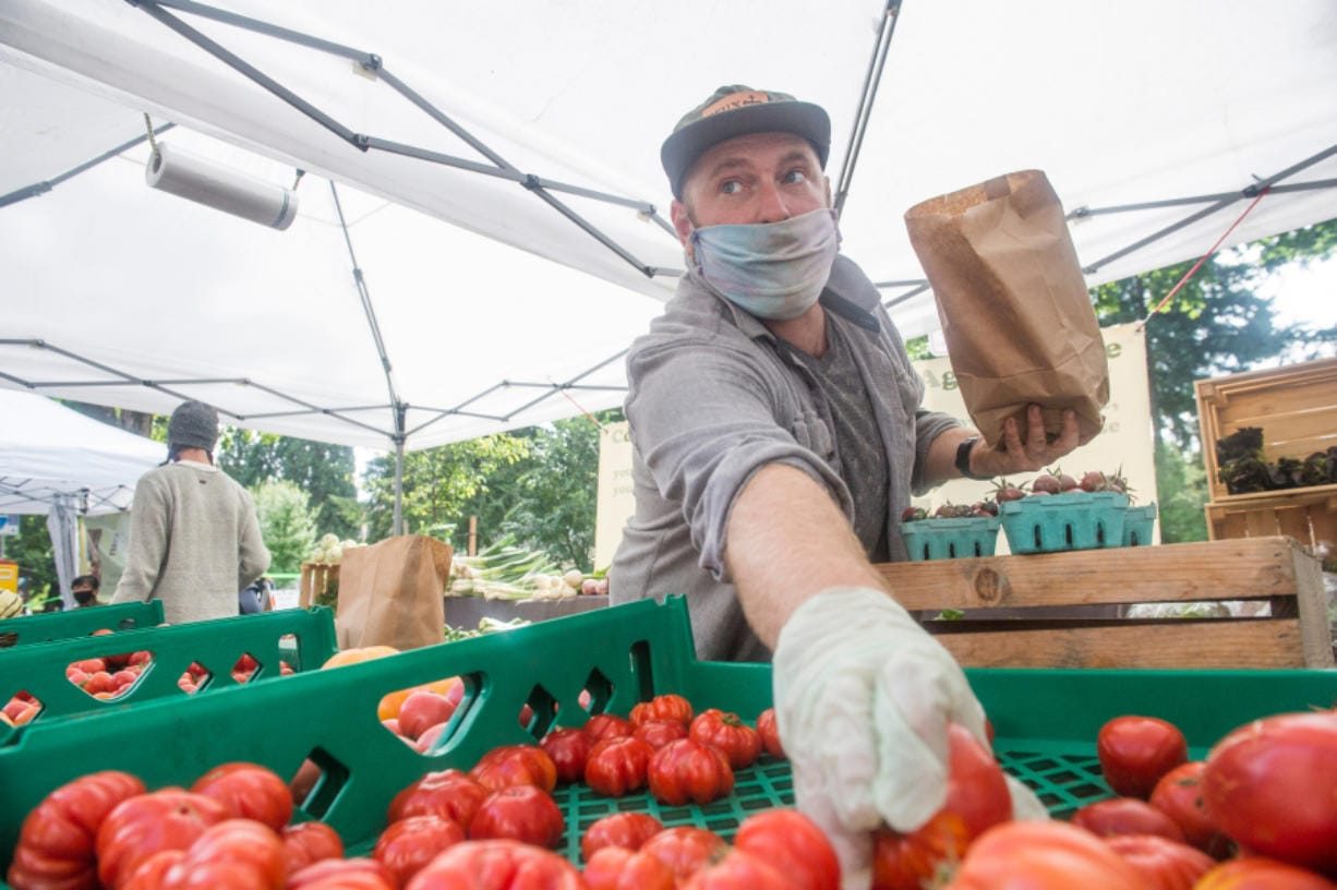 Aaron Stubbs grabs sauce tomatoes for a customer at the Quackenbush Farm booth at the Vancouver Farmers Market on Saturday. Stubbs said the booth actually fared better this summer at the market, likely due to preordered products.