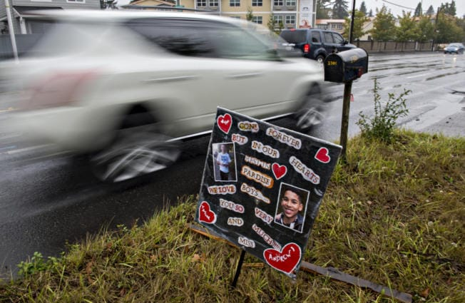 Motorists drive past a small memorial for two boys who died in January, as seen near the intersection Northeast 23rd Street and Northeast 112th Avenue. The kids -- Taylor Crepeau, 14, and Andrew Friedt, 17 -- were hit by a car while trying to cross Northeast 112th Avenue.