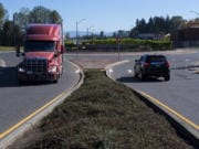 Drivers of a truck and an SUV navigate a roundabout east of Interstate 5 along South Pioneer Street in Ridgefield on Tuesday morning. Below, a motorist passes construction in Ridgefield near the intersection of South Fifth Street and Union Ridge Parkway, which is not part of the grant project but will connect to it, on Tuesday morning.