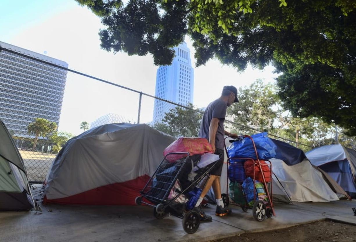 FILE - In this Monday, July 1, 2019, file photo, a homeless man moves his belongings from a street behind Los Angeles City Hall as crews prepared to clean the area. Over three days and nights this week, census takers are going to shelters, soup kitchens, mobile food van stops and other places across the U.S. where homeless people often gather. They will follow that with visits to encampments, under bridges, transit stations and other places where people live outside.