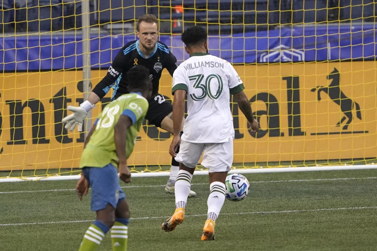 Portland Timbers midfielder Eryk Williamson (30) sets up to kick a goal against Seattle Sounders goalkeeper Stefan Frei, center, during the first half of an MLS soccer match, Sunday, Sept. 6, 2020, in Seattle. (AP Photo/Ted S.