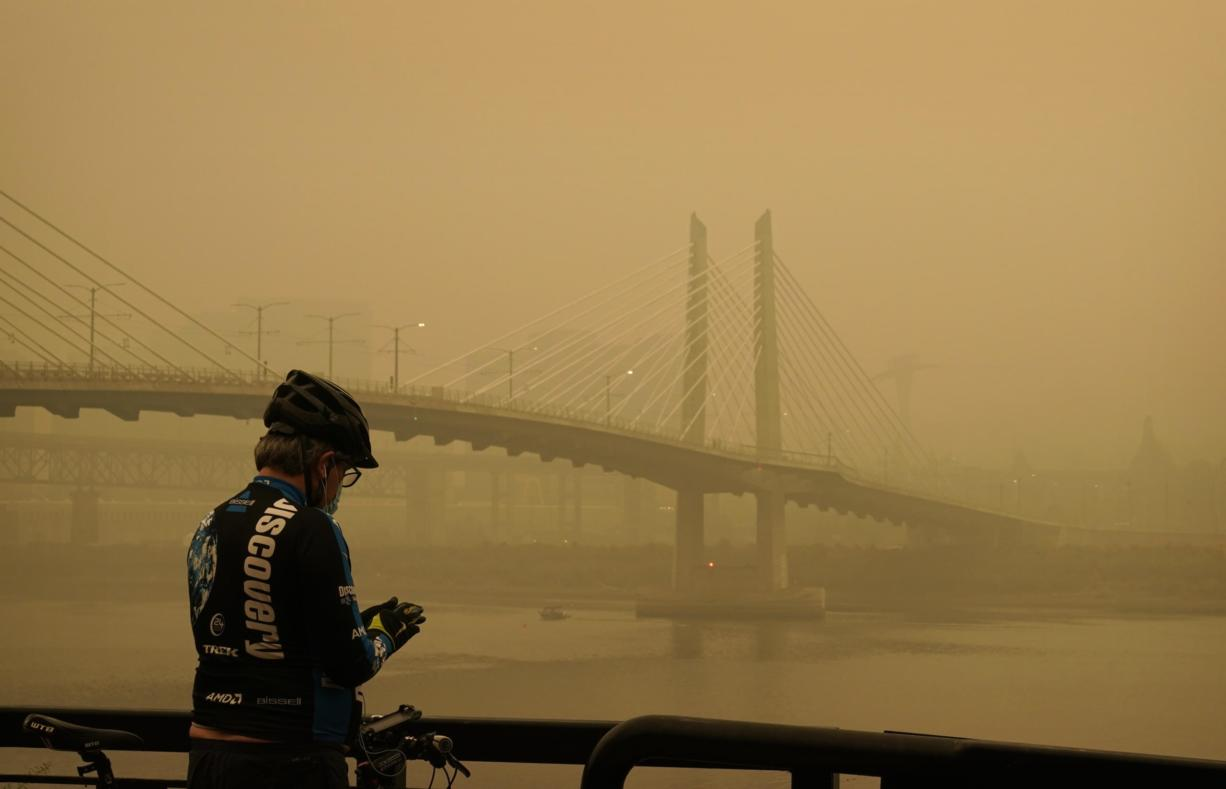 A man stops on his bike along the Willamette River as smoke from wildfires partially obscures the Tilikum Crossing Bridge, Saturday, Sept. 12, 2020, in Portland, Ore.
